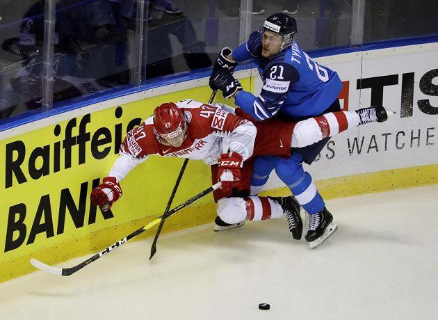 Dánský hokejista Oliver Larsen v akci během utkání mistrovství světa s Finskem. V souboji jej posílá na led Juhani Tyrvainen.