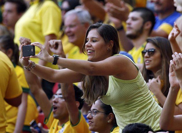 Brazilská fanynka fotí své fotbalové miláčky.