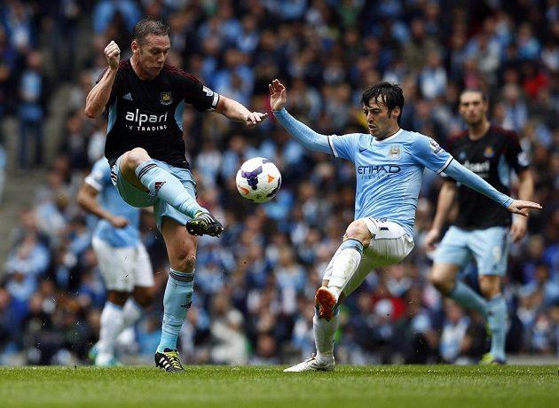 Záložník Manchesteru City David Silva (vpravo) bojuje o míč s Kevinem Nolanem z West Hamu United.