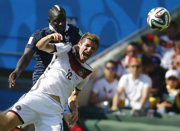 Francouzský stoper Mamadou Sakho (vzadu) v hlavičkovém souboji s Němcem Thomasem Müllerem.