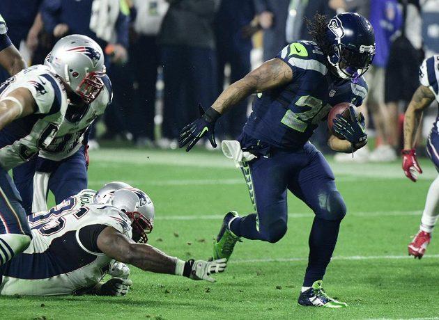 Obrana New England Patriots se snaží zastavit Marshawna Lynche.
