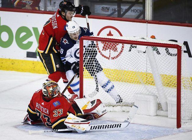 Český gólman Calgary David Rittich se ocitl na ledové ploše poté, co jej atakoval Bryan Little z týmu Winnipeg Jets v utkání NHL.