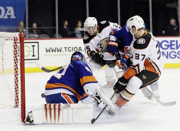 Český útočník Ondřej Kaše z Anaheimu Ducks se v utkání NHL snaží vyzrát na slovenského gólmana New Yorku Islanders Jaroslava Haláka. S číslem 37 všemu přihlíží Nick Ritchie z týmu Ducks.