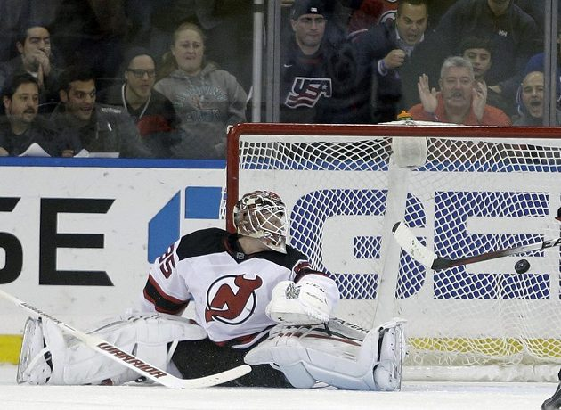 Brankář New Jersey Cory Schneider inkasuje gól z hole útočníka New Yorku Rangers Dereka Stepana.