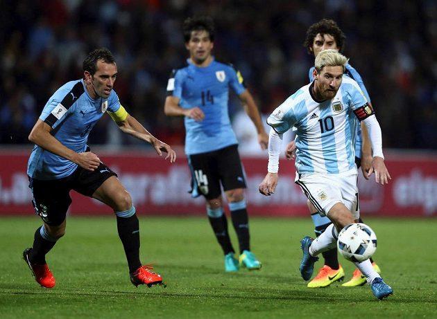 Argentinec Lionel Messi (vpravo) a Diego Godín z Uruguaye v utkání kvalifikace MS.