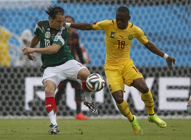 Mexický záložník Andres Guardado (vlevo) v souboji s Enohem Eyongem z Kamerunu.