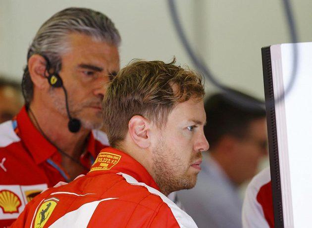 Sebastian Vettel měl v prvním tréninku v Rakousku technické problémy a sledoval dění na trati v garáži Ferrari. Vzadu přihlíží šéf týmu Maurizio Arrivabene.