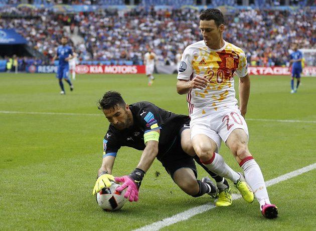 Italský brankář Gianluigi Buffon (vlevo) sbírá míč ze země před Španělem Aritzem Adurizem.