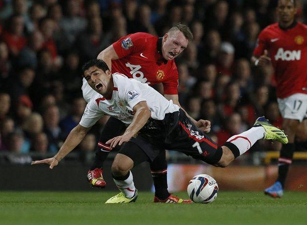 Útočník Liverpoolu Luis Suárez (v bílém dresu) padá po souboji se záložníkem Manchesteru United Philem Jonesem.