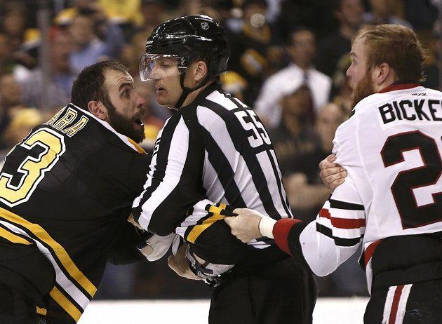 Čárový rozhodčí Shane Heyer se snaží oddělit od sebe obránce Bostonu Zdena Cháru (vlevo) a útočníka Chicaga Bryana Bickella.