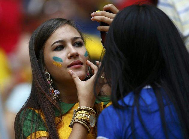 """Fanynka """"kanárků"""" maluje na svoje tváře národní barvy - zelenou a žlutou."""