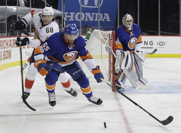 Útočník Floridy Jaromír Jágr (vlevo) bojuje o puk s Johnnym Boychukem z týmu New York Islanders. Přihlíží gólman Ostrovanů Thomas Greiss.