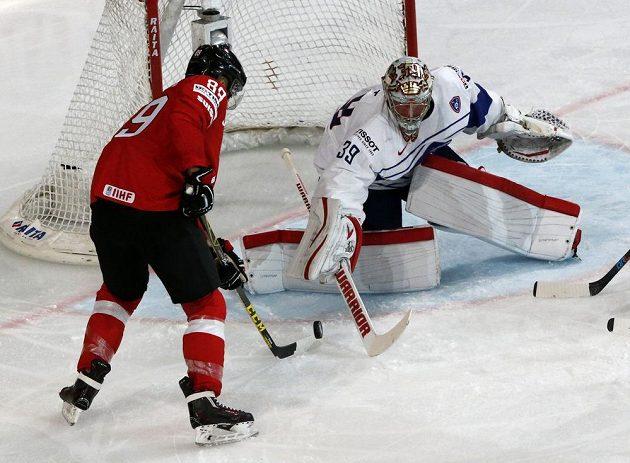 Švýcarský hokejista Cody Almond se snaží překonat francouzského brankáře Cristobala Hueta.