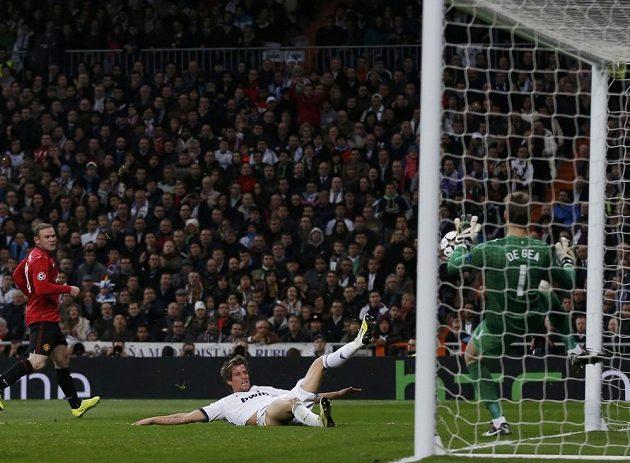 Fabio Coentrao z Realu Madrid (v bílém dresu) se snaží překonat brankáře Davida de Geu z Manchesteru United.