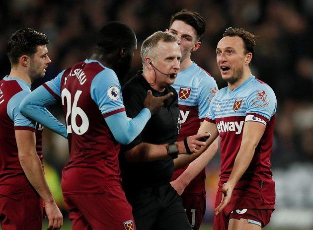 Fotbalisté West Hamu United diskutují s rozhodčím během utkání Premier League proti Liverpoolu.