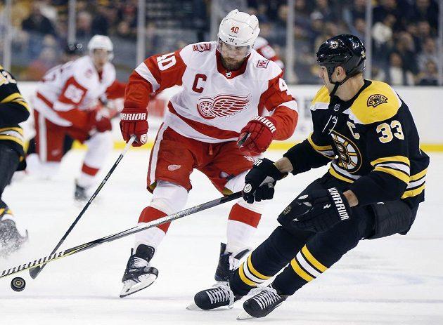 Slovenský obránce Bostonu Bruins Zdeno Chára (33) se snaží zastavit Henrika Zetterberga z Detroitu v utkání NHL.