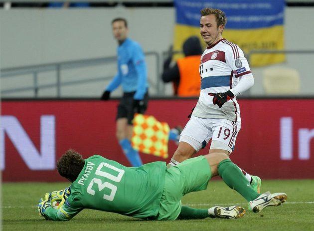 Brankář Šachtaru Doněck Andrej Pjatov chytá míč před záložníkem Bayernu Mariem Götzem.