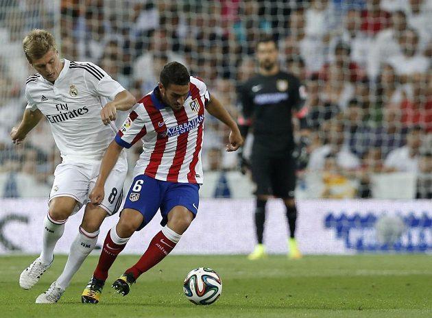 Záložník Realu Madrid Toni Kroos (vlevo) se snaží vypíchnout míč Kokemu z Atlétika.