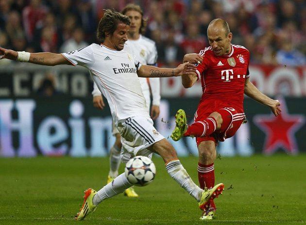 Střelecký pokus tvůrce hry Bayernu Arjena Robbena se snaží zblokovat Fabio Coentrao (vlevo) z Realu Madrid.
