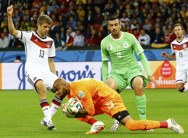 Alžírský brankář Raís Mbulhi chytá míč před německým útočníkem Thomasem Müllerem a svým spoluhráčem Essaidem Belkalemem.