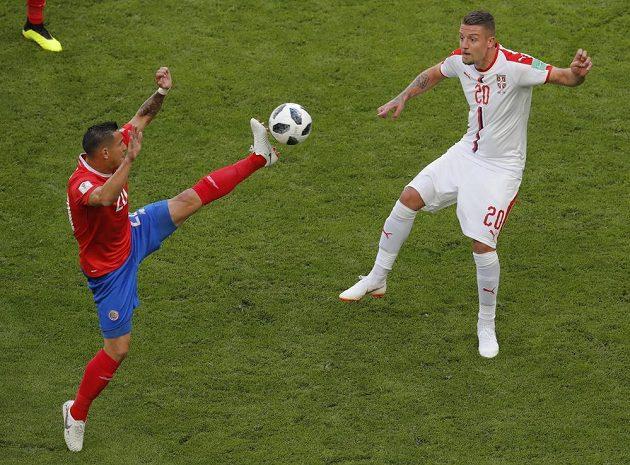 Kostarický reprezentant David Guzman (vlevo) odehrává akrobaticky míč před dotírajícím Srbem Sergejem Milinkovičem v utkání MS.