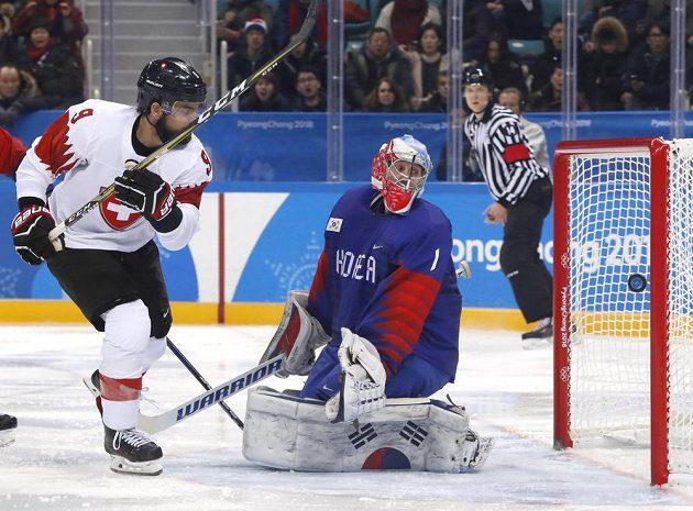 Švýcarský hokejista Thomas Rufenacht překonává korejského gólmana Matta Daltona v utkání olympijského turnaje.