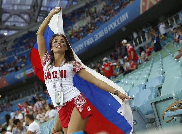 Ruská fanynka žene fotbalisty hostitelské země kupředu.