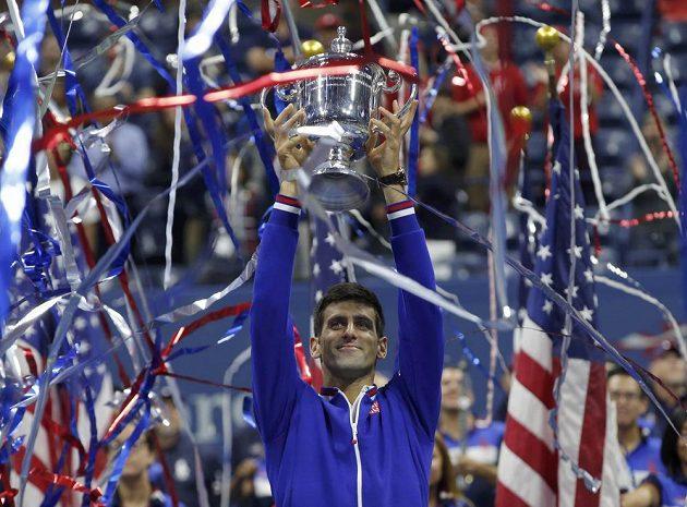 Světová tenisová jednička Novak Djokovič s trofejí pro šampióna US Open nad hlavou.