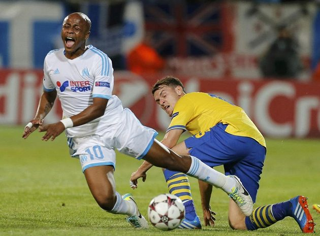 André Ayew (vlevo) z Marseille padá po souboji se záložníkem Arsenalu Londýn Aaronem Ramseym.