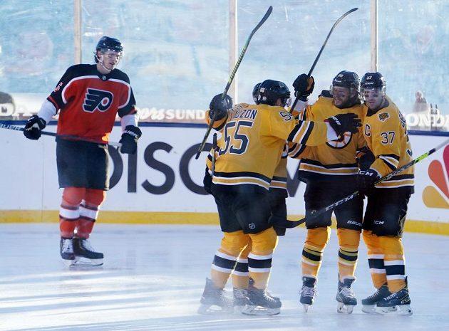 Hokejisté Bostonu Bruins slaví. Český kanonýr David Pastrňák (88) se raduje z gólu v síti Philadelphie, k přesné trefě gratulují obránce Jeremy Lauzon (55) a útočník Patrice Bergeron (37).