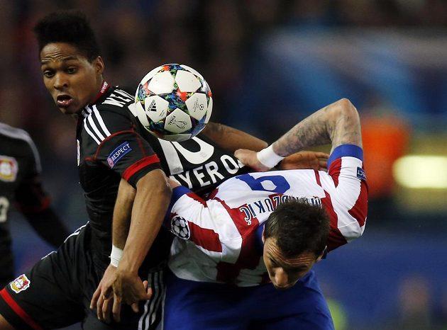 Wendell z Leverkusenu (vlevo) a útočník Atlétika Madrid Mario Mandzukič v odvetném osmifinálovém zápase Ligy mistrů.