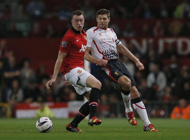 Záložník Manchesteru United Phil Jones (vlevo) v souboji se Stevenem Gerrardem z Liverpoolu.