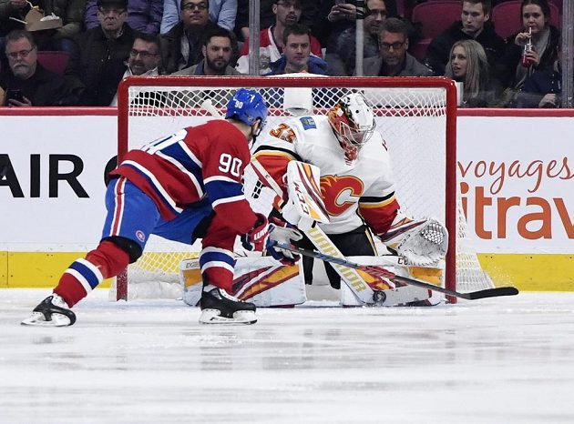Gólman Calgary David Rittich (33) kryje střelecký pokus Tomáše Tatara.
