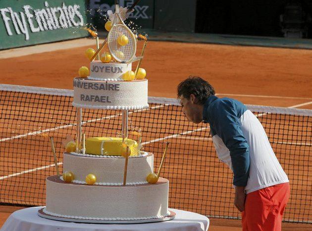 Rafael Nadal se snaží sfouknout svíčky ze svého narozeninového dortu.