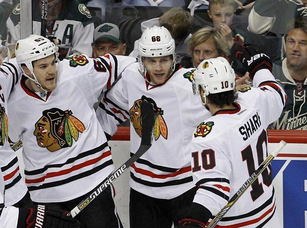 Patrick Kane (88) po vstřelení branky, která Chicagu na ledě Minnesoty zajistila výhru ve třetím zápase druhého kola play off NHL. Gratulují mu Andrew Shaw (vlevo) a Patrick Sharp.