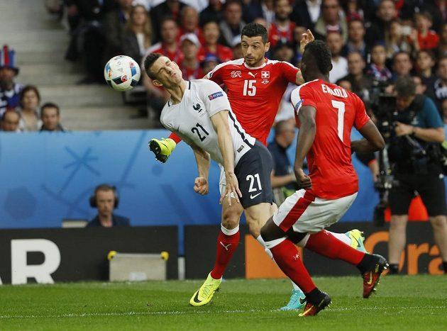 Laurent Koscielny hlavičkuje míč před Blerim Džemailim (15) ze Švýcarska.