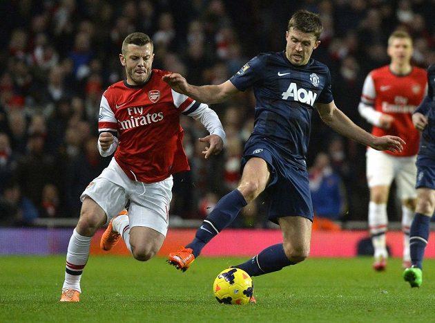 Jack Wilshere (vlevo) z Arsenalu v souboji s manchesterským Michaelem Carrickem.