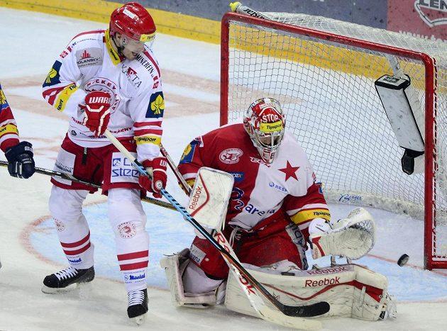 Třinecký útočník Tomáš Plíhal (vlevo) se snaží dopravit puk za záda slávistického brankáře Dominika Furcha v předehrávce 50. kola hokejové Tipsport extraligy.