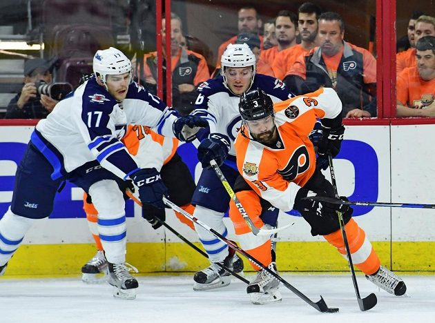 Český obránce Philadelphie Radko Gudas v souboji s hráči Winnipegu Adamem Lowrym (vlevo) a Markem Daňem.