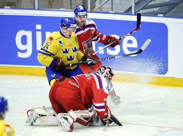 Český brankář Jakub Kovář v akci, při utkání v Umee ho atakuje Švéd Mattias Janmark-Nylén.