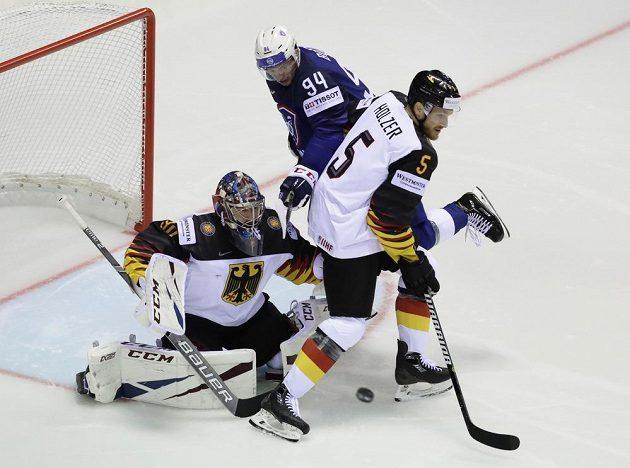 Brankář německé hokejové reprezentace Philipp Grubauer a obránce Korbinian Holzer se snaží zastavit puk mířící na německou branku. Vše sleduje Francouz Tim Bozon.