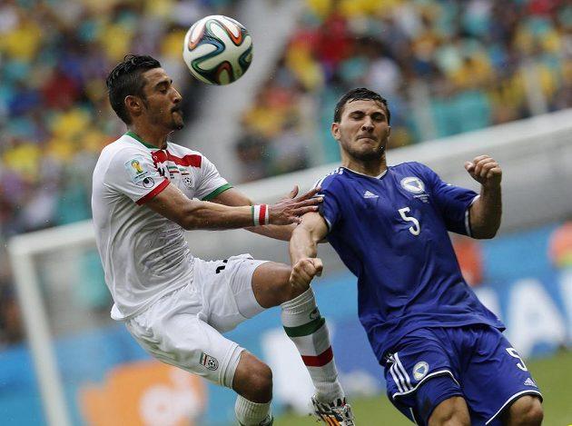 Íránský útočník Rezá Ghúčanedžhád (vlevo) bojuje o míč se Seadem Kolašinacem z Bosny a Hercegoviny.
