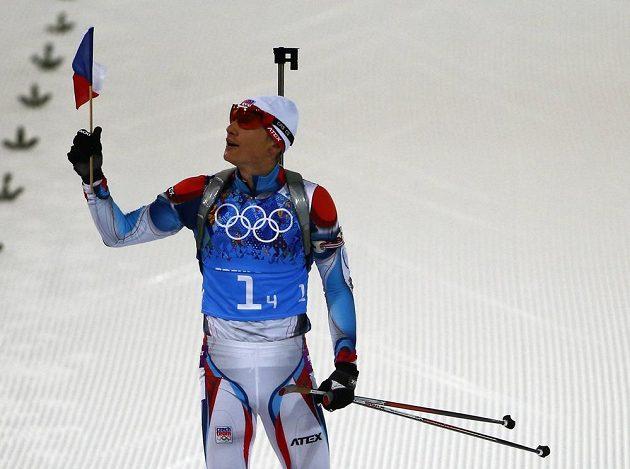 Biatlonista Ondřej Moravec s vlajkou v ruce veze český tým do cíle na stříbrné pozici.