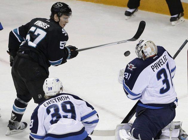 Gólman Winnipegu Ondřej Pavelec likviduje střelu útočníka San Jose Tommyho Wingelse (vlevo). Přihlíží obránce Jets Tobias Enström.