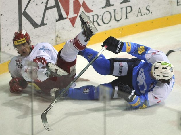 Forvard Třince Jiří Polanský (vlevo) a plzeňský Radek Duda padají po vzájemném souboji v utkání 17. kola extraligy.