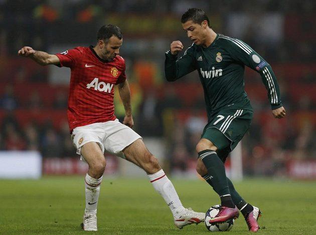 Ryan Giggs z Manchesteru United (vlevo) brání svého někdejšího spoluhráče Cristiana Ronalda, který obléká dres Realu Madrid.