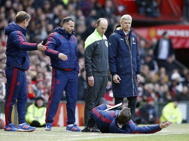 Kouč Manchesteru United Louis van Gaal leží před trenérem Arsenalu Arsénem Wengerem (vpravo), čtvrtým rozhodčím Mikem Deanem a svým asistentem Ryanem Giggsem.