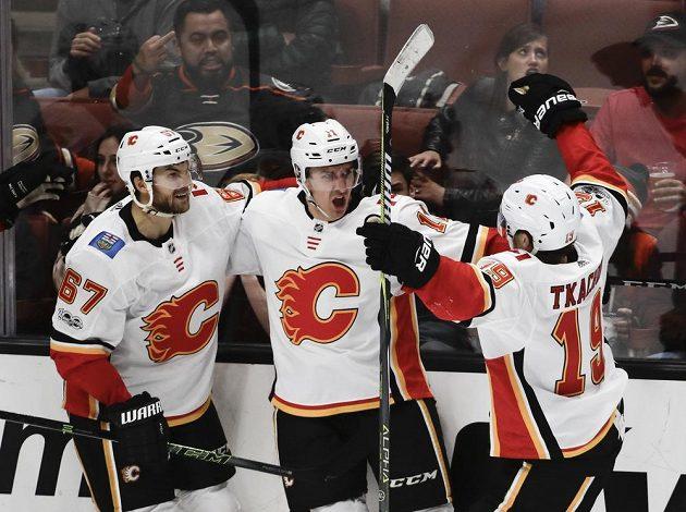 Mikael Backlund (uprostřed) z Calgary slaví gól společně s Michaelem Frolíkem (vlevo) a Matthewem Tkachukem.