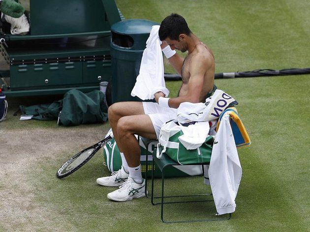 Novak Djokovič se převléká ve finále Wimbledonu.