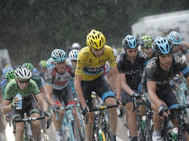 Christopher Froome (ve žlutém) během páteční etapy Tour de France, kterou poznamenaly i značné deštivé přeháňky.